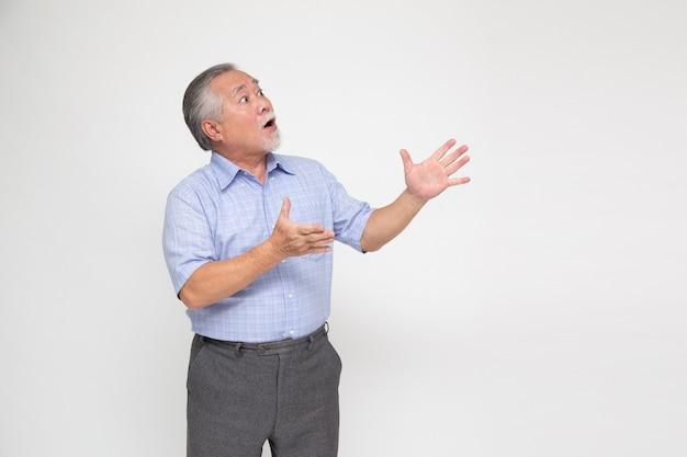 Retrato de homem asiático sênior gritando animado em pé isolado sobre uma parede branca.