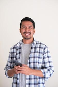 Retrato de homem asiático sorrindo amigavelmente enquanto segura um telefone celular