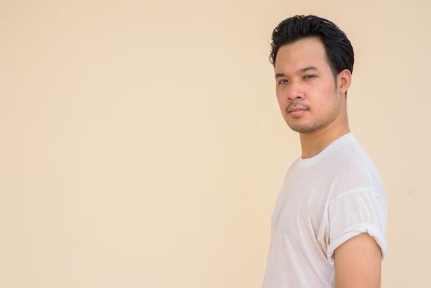 Retrato de homem asiático vestindo camiseta branca casual contra um fundo liso ao ar livre