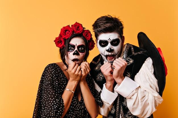 Retrato de homem assustado e mulher com flores no cabelo. jovens chocados com arte facial