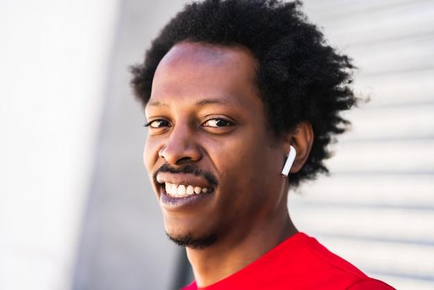 Retrato de homem atleta afro em pé ao ar livre na rua. esporte e estilo de vida saudável.