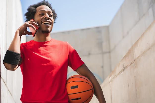 Retrato de homem atleta afro falando ao telefone e relaxando após o treino ao ar livre. esporte e estilo de vida saudável.