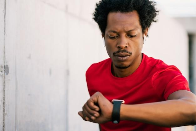 Retrato de homem atleta afro, verificando as horas em seu relógio inteligente. esporte e conceito de estilo de vida saudável.
