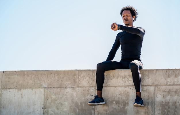Retrato de homem atleta afro, verificando as horas no relógio inteligente. esporte e conceito de estilo de vida saudável.