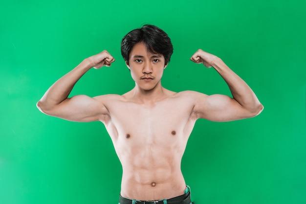 Retrato de homem atlético forte mostrando corpo musculoso, na parede verde