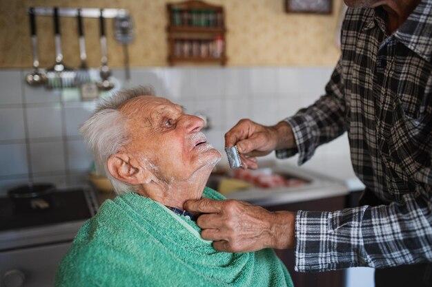 Retrato de homem barbeando o pai idoso dentro de casa em casa.
