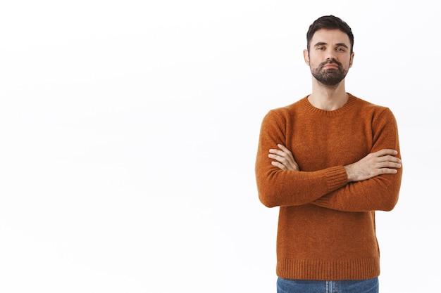 Retrato de homem barbudo adulto bonito e confiante com ego enorme, parece orgulhoso e orgulhoso, peito de braços cruzados como um verdadeiro profissional, sente-se poderoso e assertivo, sorri satisfeito, parede branca