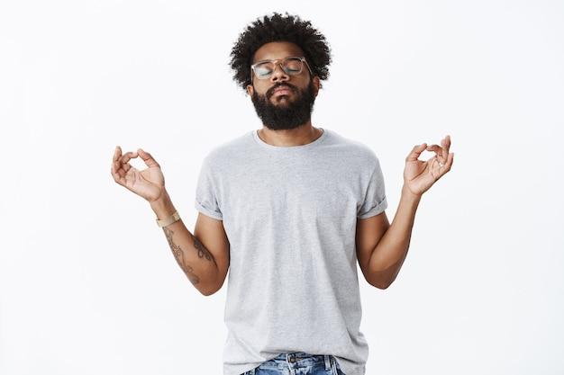 Retrato de homem barbudo afro-americano adulto calmo e tranquilo com tatuagens e olhos fechados penetrantes, em pose de lótus com orbes do nirvana, fazendo ioga