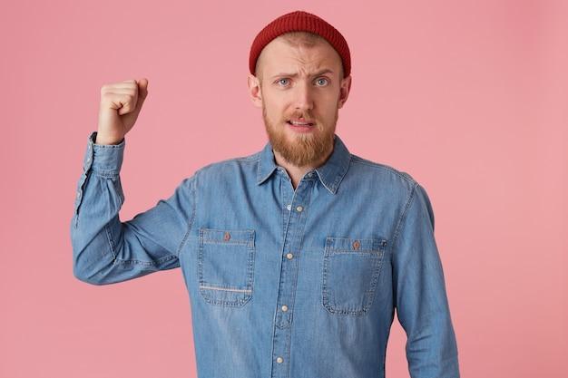 Retrato de homem barbudo agressivo balançando o punho, demonstra um gesto guerreiro, vestindo camisa jeans, isolado