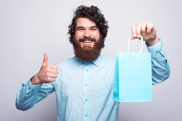 Retrato de homem barbudo alegre em casual mostrando o polegar para cima gesto e sacola de compras azul