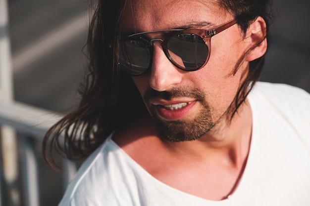 Retrato de homem barbudo atraente usando óculos de sol na moda