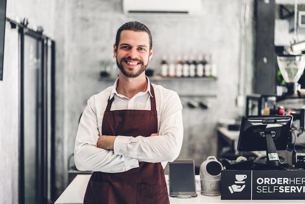 Retrato de homem barbudo bonito barista empresário pequeno empresário sorrindo atrás da barra de balcão em um café