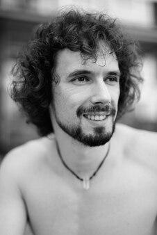 Retrato de homem barbudo bonito com cabelo encaracolado sem camisa