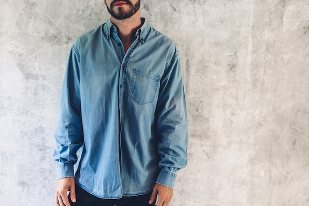 Retrato de homem barbudo bonito com camisa azul