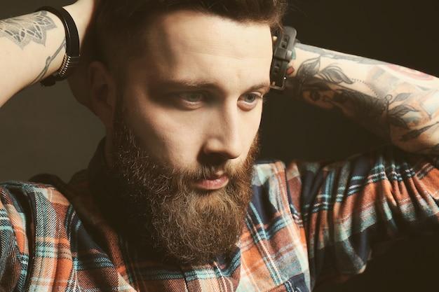Retrato de homem barbudo bonito em fundo preto, close-up