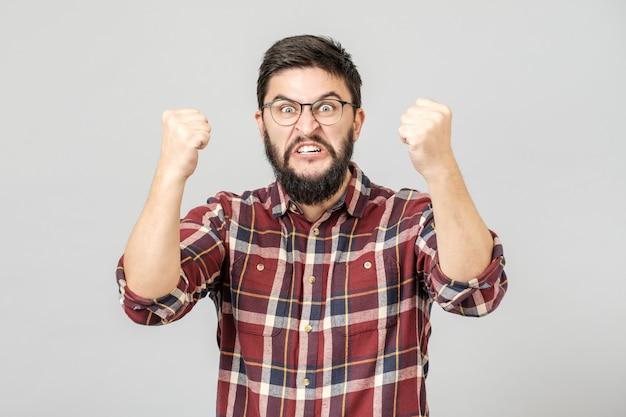 Retrato de homem barbudo bonito, gritando e cerrando os punhos levantados enquanto triunfava do sucesso