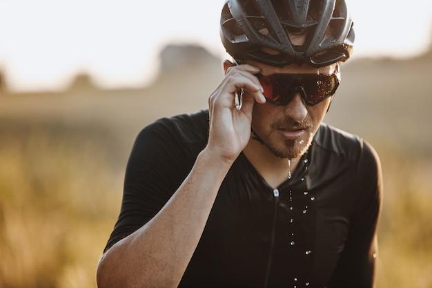 Retrato de homem barbudo com capacete preto e óculos espelhados, sentindo-se cansado por causa do treinamento duro.