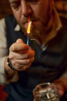 Retrato de homem barbudo com cinzeiro acende um cigarro, vista do close up. cultura de fumar tabaco, sabor específico. fumante masculino lazer no escritório