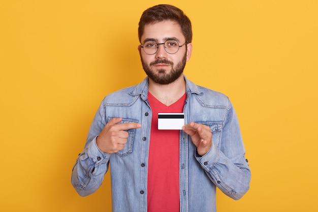 Retrato de homem barbudo confiante apontando com o dedo indicador para cartão de crédito, pagando com cartão para compra