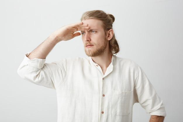 Retrato de homem barbudo confiante bonito com cabelos loiros, segurando a mão na testa como se estivesse olhando para longe como marinheiro ou capitão