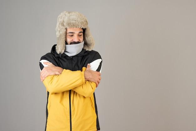 Retrato de homem barbudo congelado em roupas quentes em pé e posando.