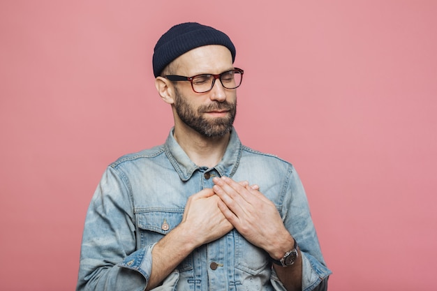 Retrato de homem barbudo de aparência amigável com os olhos fechados, mantém as mãos no peito, usa jaqueta jeans