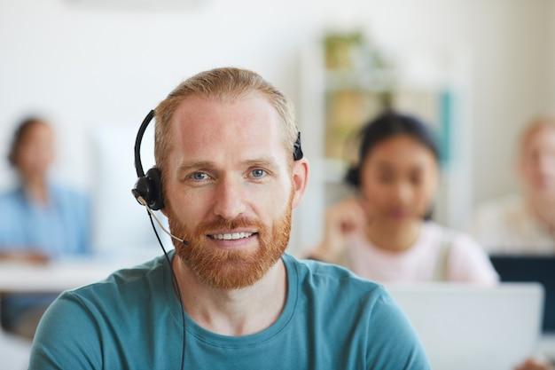 Retrato de homem barbudo em fones de ouvido sorrindo, ele trabalhando na central de atendimento ao cliente