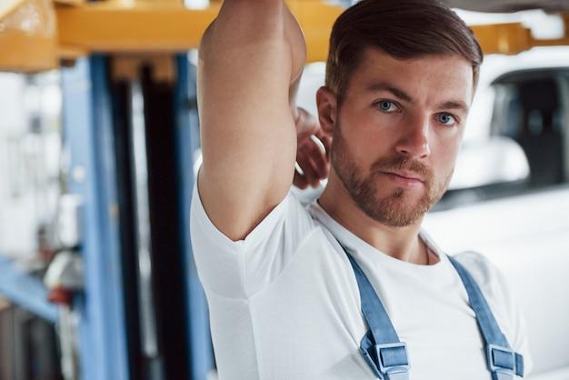 Retrato de homem barbudo. empregada com uniforme azul trabalha no salão automóvel.