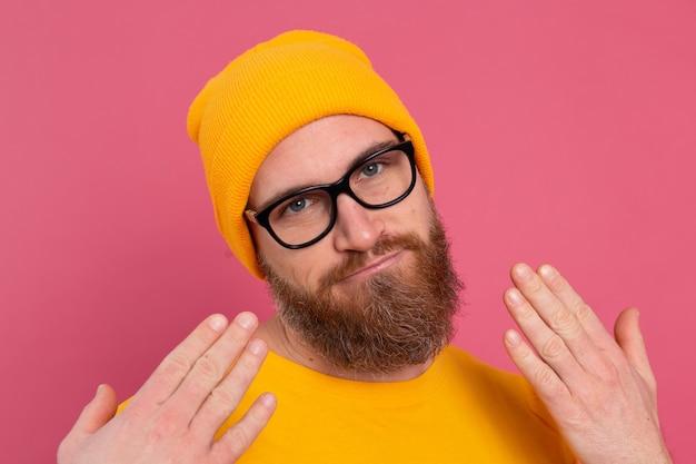 Retrato de homem barbudo europeu bonito elegante com chapéu de camisa amarela casual e óculos no fundo rosa