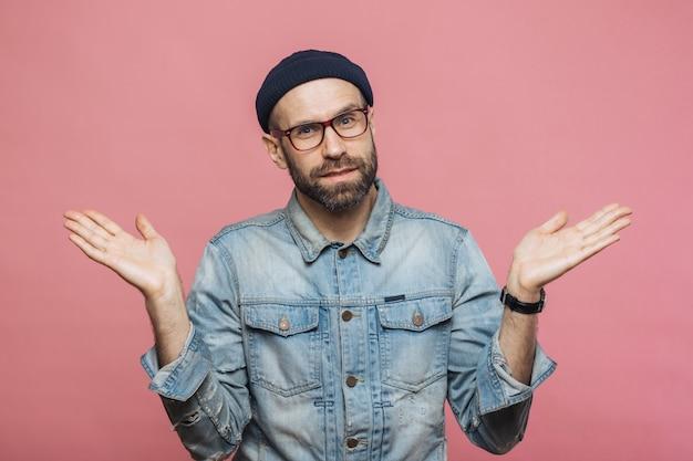 Retrato de homem barbudo hesitante com expressão duvidosa, encolhe os ombros os ombros, veste jaqueta jeans