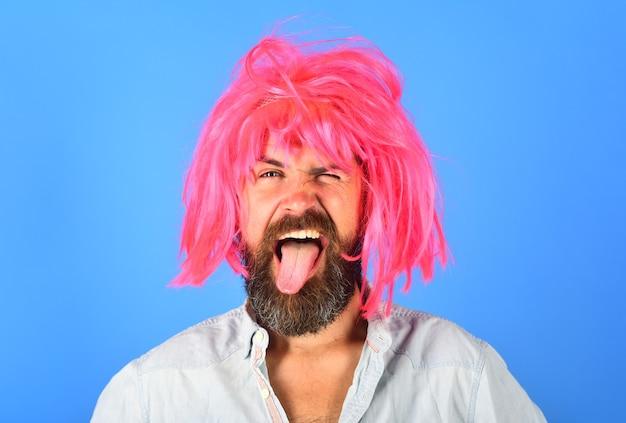 Retrato de homem barbudo. homem sorridente mostra a língua. homem barbudo sorridente. retrato de homem sorridente. isolado. peruca. cabelo colorido. emoções. caras engraçadas.