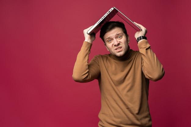 Retrato de homem barbudo jovem estressado infeliz segurando laptop acima da cabeça enquanto stsanding isolado sobre fundo rosa.
