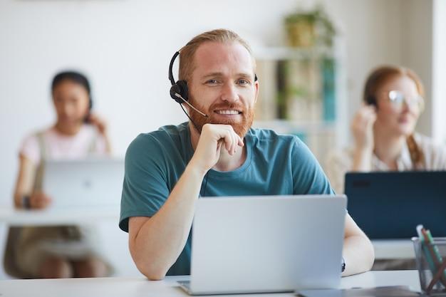 Retrato de homem barbudo maduro em fones de ouvido sorrindo enquanto trabalhava na mesa com o laptop