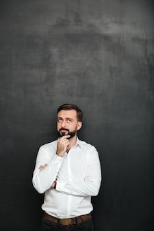 Retrato de homem barbudo morena de camisa branca, tocando seu queixo pensando ou lembrando sobre cinza escuro