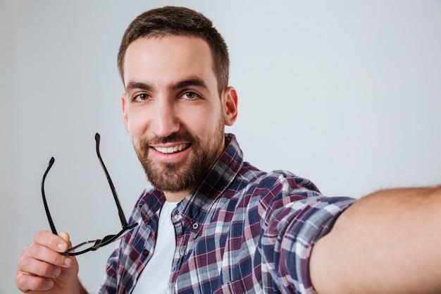 Retrato de homem barbudo na camisa fazendo selfie