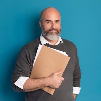 Retrato de homem barbudo segurando documentos