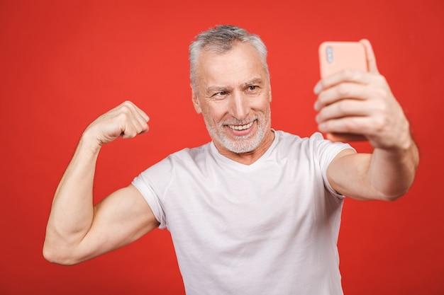 Retrato de homem barbudo sênior feliz mostrando o bíceps e tomando selfie no smartphone, isolado. esporte e conceito saudável.