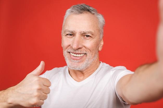 Retrato de homem barbudo sênior feliz mostrando os polegares e tomando selfie no smartphone, isolado.