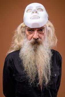 Retrato de homem barbudo sênior segurando uma máscara branca