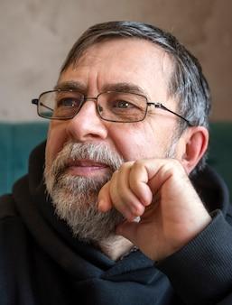 Retrato de homem barbudo sênior usando óculos dentro de casa