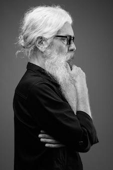 Retrato de homem barbudo sênior vestindo uma camisa preta cinza em preto e branco