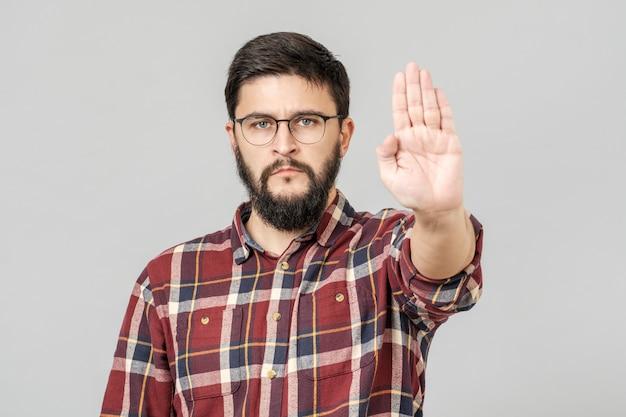 Retrato de homem barbudo sério mostrando o gesto de parada com a palma da mão