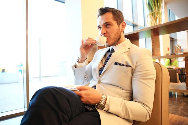 Retrato de homem bem sucedido bonito beber café sentado na cafeteria, homem de negócios, tomando café da manhã no saguão do hotel.