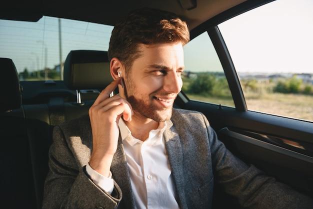 Retrato de homem bem sucedido, vestindo terno e earpod tendo conversa móvel, enquanto volta sentado no carro de classe executiva