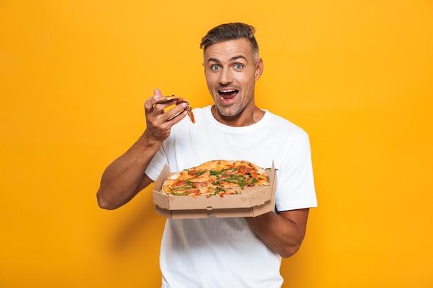 Retrato de homem bonito 30 anos em uma camiseta branca segurando e comendo pizza em pé isolado no amarelo