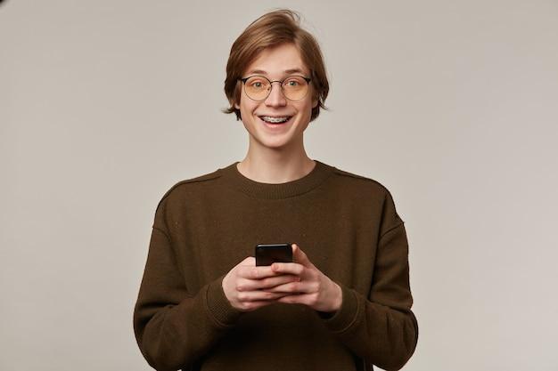 Retrato de homem bonito, adulto com cabelo loiro. vestindo óculos e suéter marrom. tem colchetes.