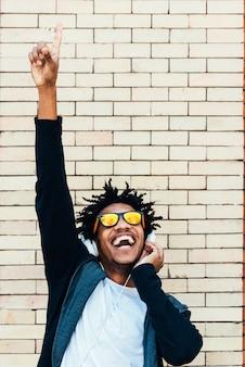 Retrato de homem bonito afro ouvindo música na rua.