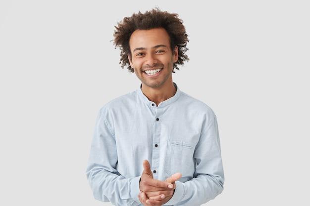 Retrato de homem bonito alegre mantém as mãos juntas, sorri amplamente, vestido com uma camisa elegante