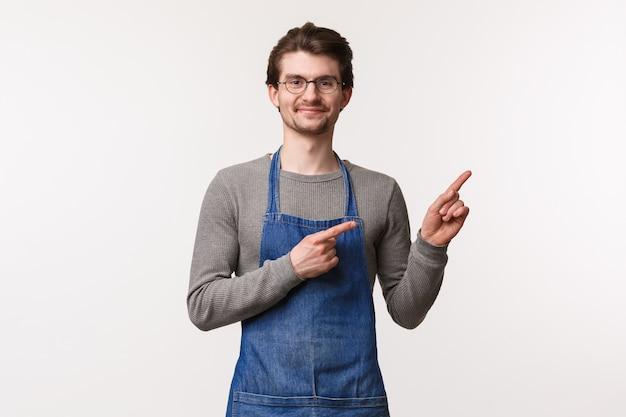 Retrato de homem bonito amigável confiante no avental, o proprietário da empresa convida os clientes a visitarem seu café, trabalhando com a equipe apontando o canto superior direito, sorrindo a câmera,