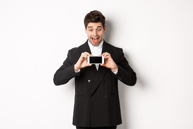 Retrato de homem bonito animado mostrando a tela do smartphone